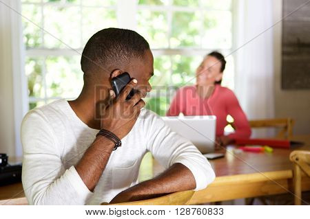 African Guy Making A Phone Call And Looking Back At Woman