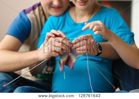 Pregnant wife and husband knitting on spokes baby clothes for your future baby. Man learns to knit. Loving couple at home.