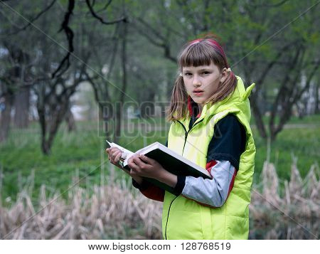Teen girl in the park with a book. Concept - exam preparation, difficulty learning, school. The girl has her hair dyed red. Bright jacket. Park, spring or autumn
