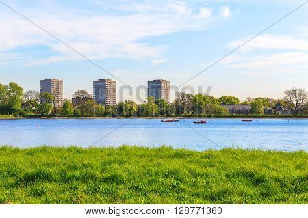 Spring view of Stock Newington West Reservoir Hackney London with green grass blue sky and a few floating boats