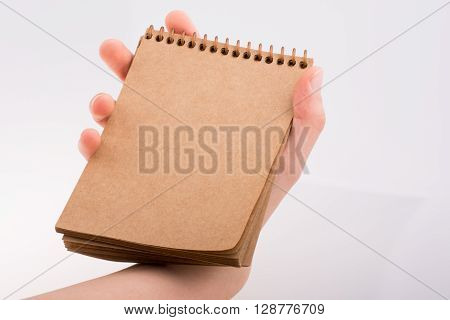 Hand holding a brown spiral notebook on a white background