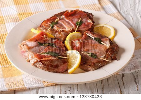 Saltimbocca Veal With Sage, Ham And Slices Of Lemon Close-up. Horizontal