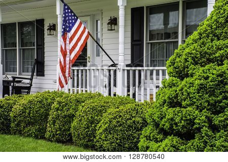 front porch of white colonial home with black shutters rockers and door flying American flag