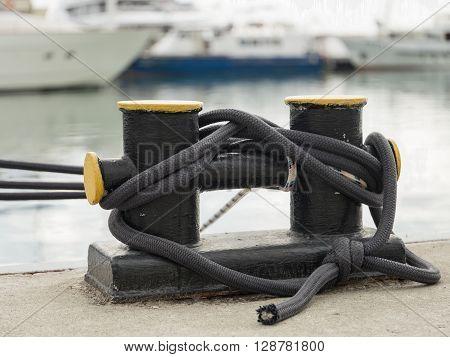 Bollard on a wharf. Ship's rope may be secured to bollard.