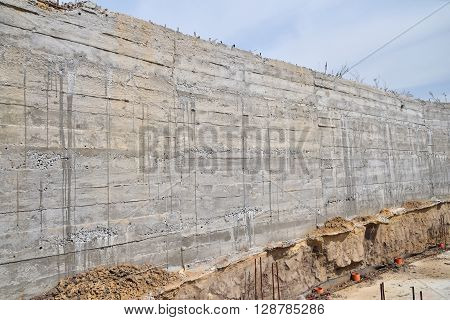 Concrete wall texture with wooden pattern impress from wooden form board shuttering and with sags of cement at construction site