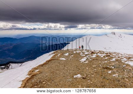 Family Over Beautiful Mountains In Wintertime. Cute Family Silhouettes In Colorful Winter Clothes An