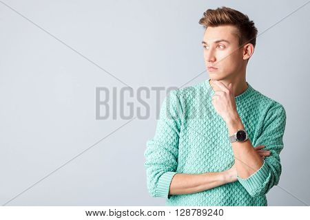 Waist up portrait of attractive young man making serious decision. He is standing and looking aside pensively. The man is touching hand to his chin. Isolated and copy space in left side