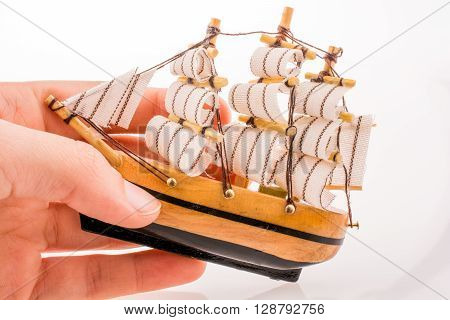 Hand holding a Little model sailboat on a white background