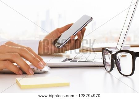Closeup of business woman hands using cell phone and laptop on white desktop with glasses and stickers. Side view of business woman hand checking mail on her smart phone at office desktop