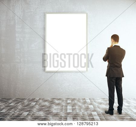 Thoughtful businessman looking at hanging picture frame in room with concrete wall and tile floor. Mock up 3D Rendering