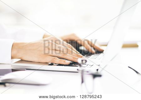 Side view of woman's hands using laptop for business purposes. Female accountant working on laptop. Closeup of woman using laptop to work on project