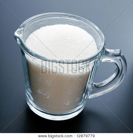 A glass measuring cup with sugar