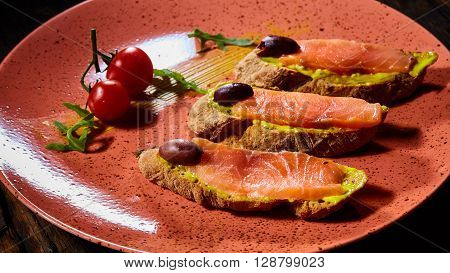 Delicious homemade smoked salmon gluten free canape garnished with tomatoes and olives