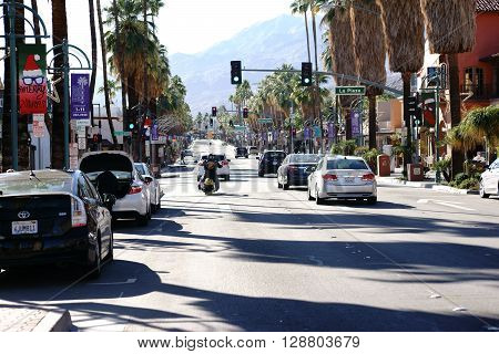 PALM SPRINGS, VEREINIGTE STAATEN - DEZEMBER 24: Road traffic with cars and a motorcycle at a traffic light intersection of Commercial Street Canyon Drive on December 24 2015 in Palm Springs.