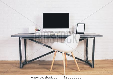 Front view of designer desk with blank computer screen and modern chair on white brick background. Mock up