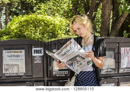 Vail, USA - September 10, 2015: Blonde young woman focused reading the local newspaper by a stand in Vail, Colorado