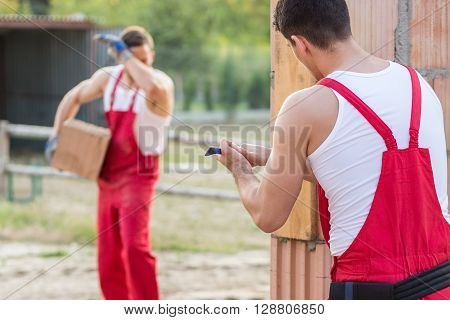 Two young building workers in red overalls performing construction work