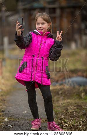Little girl makes selfie on phone, outdoors.