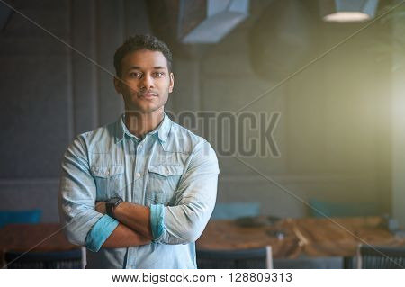 Handsome young Arabian man is standing and posing in cafe. He is looking at camera with confidence. His arms are crossed. Copy space in right side