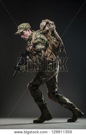 Soldier Man Hold Machine Gun On A  Dark Background