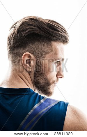 Attractive young sportsman is standing in profile. He is looking forward with inspiration. Isolated on background