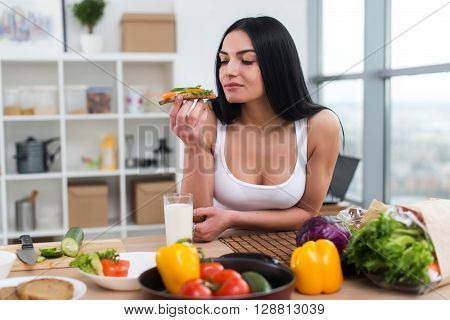 Young female standing in kitchen leaning at wooden counter, having sandwich and a glass of milk for lunch