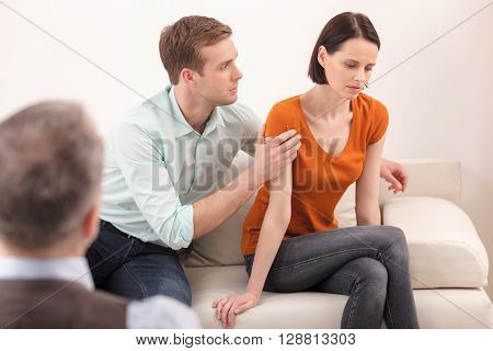 Married couple is trying to solve their problems in psychologist office. The woman feels insult. The man is embracing her with love and apology