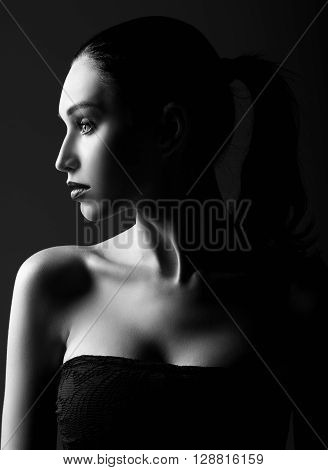 Studio shot: dramatic portrait of a beautiful young woman. Profile view. Black and white