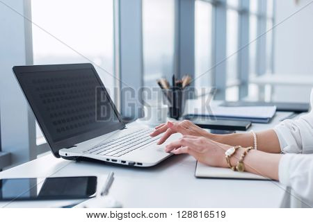 Female worker using laptop in office, working with new project. Woman blogging at home as a freelancer