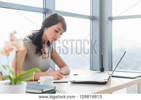 Work day of busy office manager, writing business plan in her notebook, working at work table