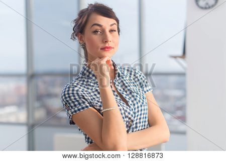 Close-up portrait of an elegant ambitious young woman, holding arms crossed, wearing checkered shirt