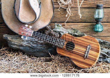 Still life photography with ukulele with american west rodeo brown felt cowboy hat and traditional in vintage ranch barn background