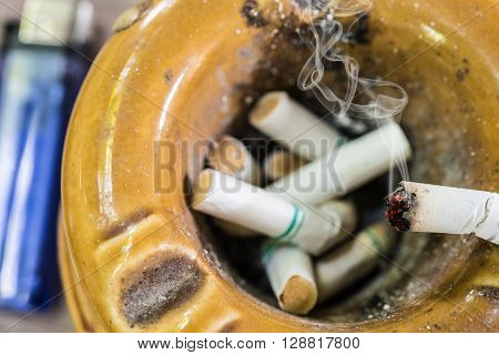 Cigarette on ashtray with smoke on cigarette butts background Social issues smoking addict concept