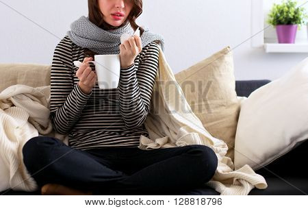 Portrait of a sick woman blowing her nose while sitting on the sofa.