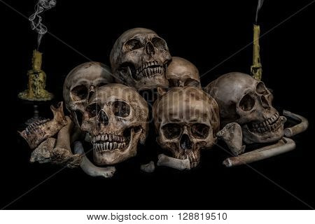 Pile of skulls and bones with two candles and smoke on black background. Genocides concept still life style.