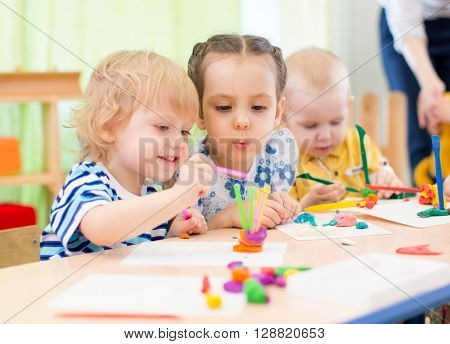 happy kids doing arts and crafts in day care centre poster