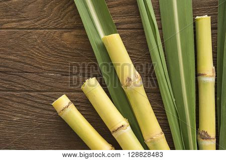 Fresh sugarcane cut into pieces on a wooden table with leaves and cane top view.