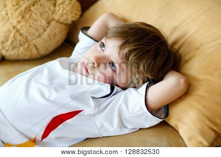 Little blond preschool kid boy after watching soccer european cup game on tv. Sad child about lost game of his football team. Champions league concept.