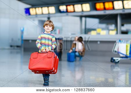 Cute little kid boy with red suitcase on international airport. Mother and daughter on background, happy family wating for flight and going on vacations.