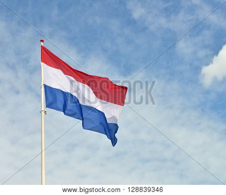 Flag of Netherlands against the blue sky.
