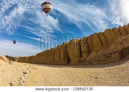 Huge multi-colored balloon over the hot desert. Stone desert near the seaside resort of Eilat.