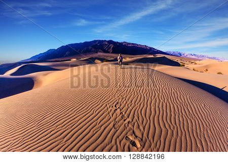Sunrise in the orange sands of the desert Mesquite Flat, USA. Woman - photographer is among the gently sloping sand dunes