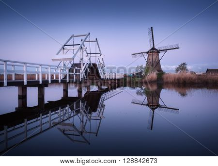 Spring landscape with beautiful traditional dutch windmills near the water channels with drawbridge and reflection in water at sunrise in famous Kinderdijk, Netherlands