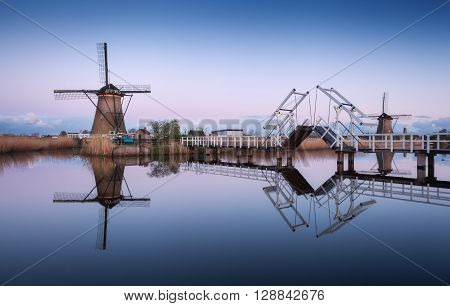 Landscape With Traditional Dutch Windmills And Drawbridge At Sunrise