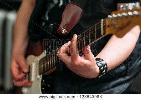 Musician playing six string electric guitar in sound recording studio. Rocker playing on electric guitar, closeup. Musical instrument closeup.