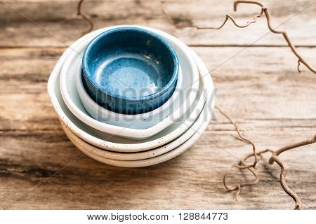 Flat lay set of handmade ceramic crockery. Top view of unusual creative bowls on  old wooden background. Stack of empty ceramic dishes  over wooden table with free space. pottery concept