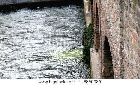 Fluss fließt entlang einer Mauer aus rotem Stein