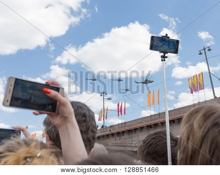 Moscow - May 7 2016: Military helicopters during the final rehearsal of the Victory parade and people are making photos May 7 2016 Moscow Russia