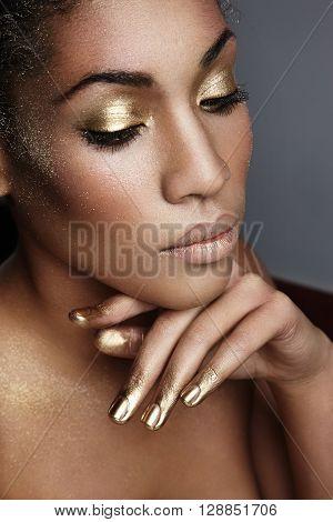black woman with golden evening makeup closeup