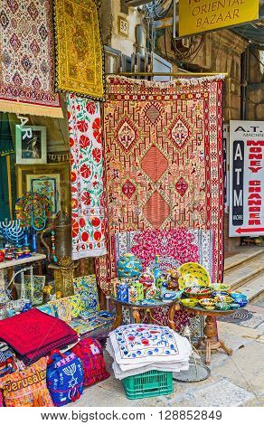 JERUSALEM ISRAEL - FEBRUARY 18 2016: The old market stall on Via Dolorosa offers colorful embroidered tableclothes napkins pillowcases and other handmade gifts on February 18 in Jerusalem.